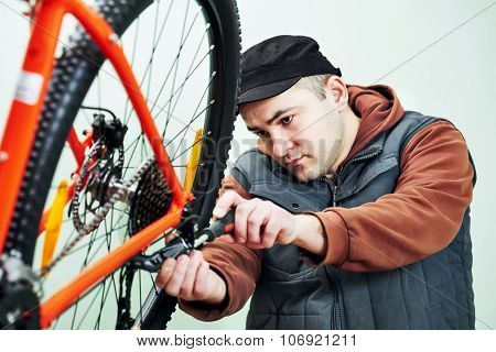 Bike maintenance. mechanic serviceman repairman installing assembling or adjusting bicycle gear on wheel in workshop