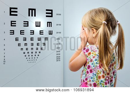 Little Girl Looking At Vision Test Chart.