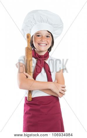 Closeup of smiling little boy dressed as chef isolated on white background. Little chef holding rolling pin and looking at camera. Happy cute boy dressed a cook.