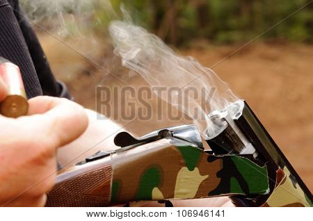 Smoking gun concept,  a double barreled over/under shotgun immediately after firing with shallow depth of field focused on the smoke leaving the breech