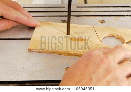 Closeup of a woman's hands working with a band-saw to cut an intricate shape in a piece of plywood
