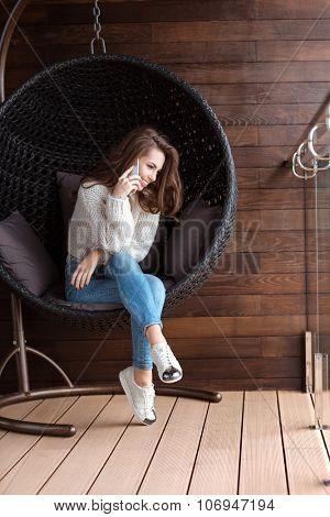 Cute positive girl sitting in bubble chair and talking on the cell phone