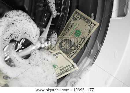 Laundering of dirty money in washing machine, close up