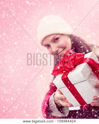Young girl in snow gives a christmas gift with red bow and ribbon.