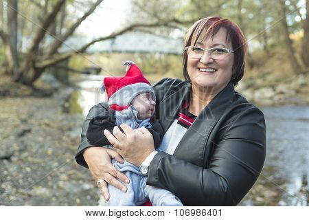 grandmother holding a baby with a bagel in the autumn forest