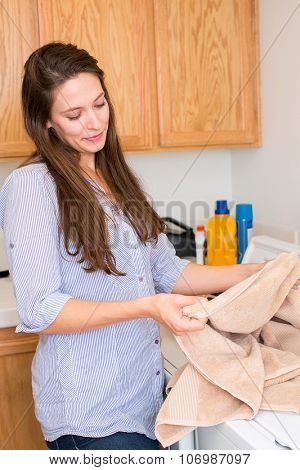 Happy woman doing laundry in her home