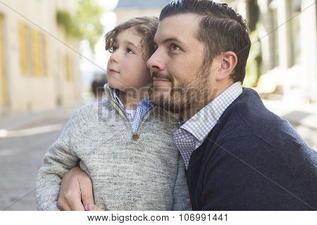 A Young dad with her son ooutside in a urban street poster