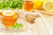 tea with mint honey cinnamon and lemon on wood backgroundwarm toning selective focus poster