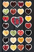 Large mixed fruit background in heart shaped dishes with fruits high in antioxidants, vitamin c and dietary fiber. poster