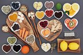 Large health food and herb selection for cold and flu remedy including foods high in antioxidants and vitamin c on olive wood boards and spoons over grey background. poster