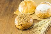 bread and wheat on the wood background warm toning selective focus poster