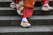 The closeup of the traditional okobo wooden sandals of a Japanese Maiko (Geisha in training). Kyoto Japan poster