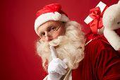 Santa carrying sack with xmas gifts poster