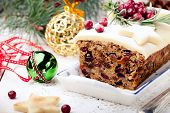 Traditional Christmas Fruit Cake pudding with marzipan and cranberry and rosemary decor on a Christmas decoration background poster