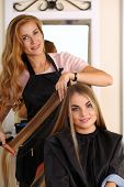 Beautiful blonde female hairdresser holding comb and hair lock making new hairdo to pretty smiling customer woman with sample book in hands. Hairdresser salon barber shop perfect look concept poster