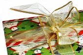 Tight shot of beautiful golden bow on green Christmas wrapping against white background. poster