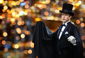 performance, circus, show concept - magician in top hat and cape showing trick with magic wand over nigh lights background poster