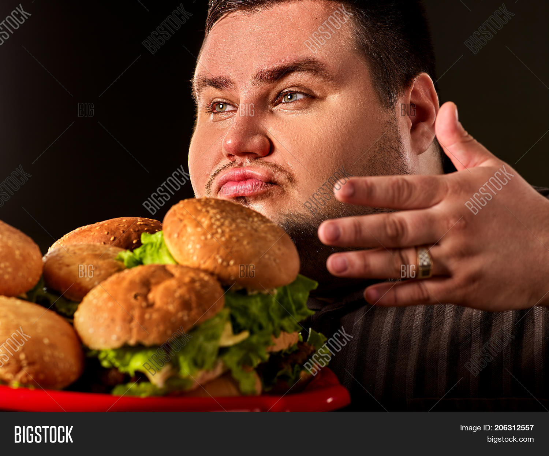 Fat black guy eating a cheeseburger