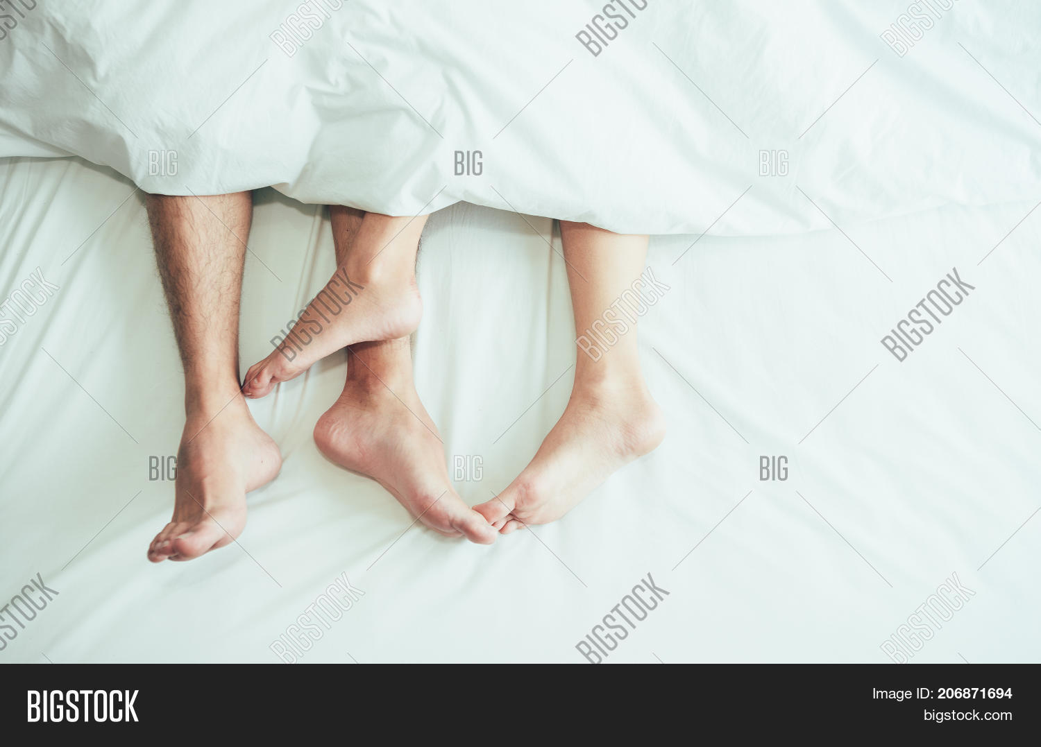 The Feet Or Foot Of Couples Sleeping On The Bed And Cover By The White Blanket