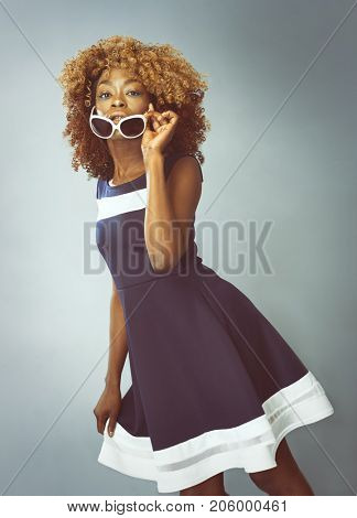 African Caribbean Woman with afro hair with vintage seventies clothing holding sunglasses