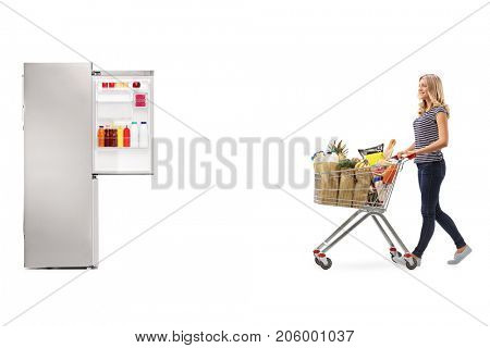 Full length profile shot of a young woman pushing a shopping cart filled with groceries towards an open fridge isolated on white background