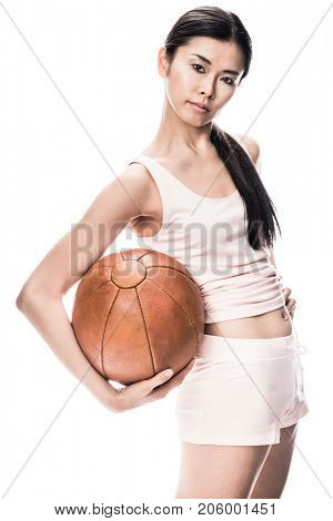 Young fit Asian woman looking at camera while holding brown medicine ball