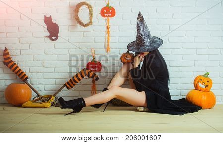 Halloween holiday celebration concept. Woman in witch hat and coat sitting on floor. Girl with pumpkins striped stockings black cat on wall. Evil spell and magic. Tradition and traditional symbols.