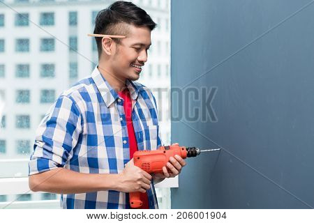 Asian do-it-yourself handyman drilling at wall in skyscraper building