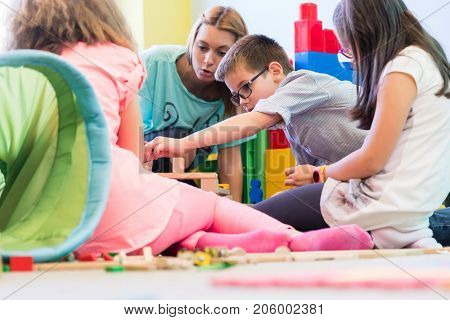 Cute pre-school boy cooperating with his colleagues at the construction of a structure, made of wooden toy blocks under the guidance of a young kindergarten teacher