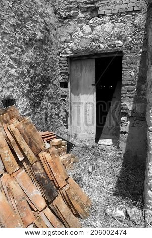 ruined door of an old shack with in foreground some roofing-tiles