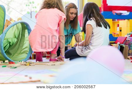 Young dedicated kindergarten teacher coordinating a fun activity for the kids during interactive playtime in the classroom