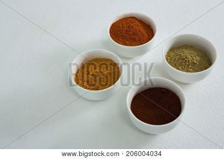 Close-up of spices powder in bowl on white background