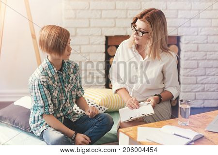 Professional help. Pleasant helpful psychologist having a session and talking with a school boy while listening to his problems