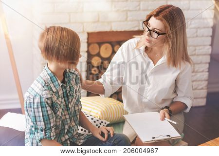 I will help you. Pleasant professional psychologist talking with a school boy and trying to help him while having a psychological session