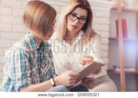 Fill in the form. Professional nice female psychologist giving a school boy a test while having a consultation and trying to help him