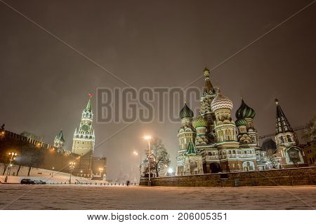 Panorama landscape of Kremlin wall with The Spasskaya tower and Saint Basil Cathedral on red square in winter night on Christmas day at Moscow, Wide shot of Beautiful architecture with street road shining by light and lamp under black sky its most popular