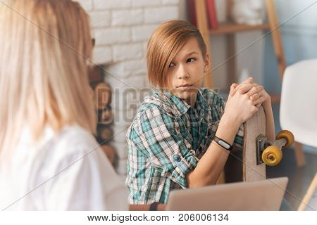 Teenager problem. Troubled schooldoy holding his skateboard and talking with his psychologist during a psychological session
