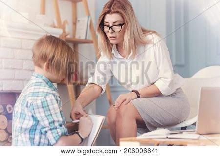Here it is. Professional psychologist testing a teenager schoolboy and having a psychological session while helping him with filling in the test paper