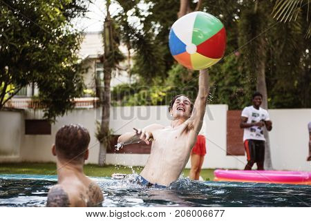 Diverse men playing beach inflatable ball in swimming pool