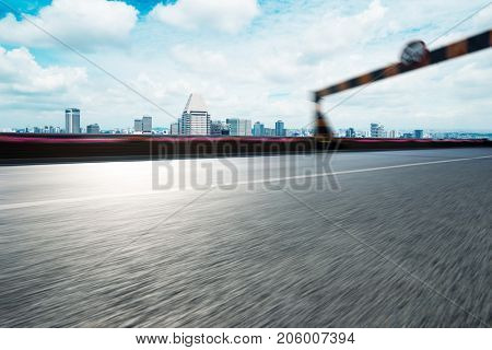 blurry empty asphalt road with road sign and cityscape of nanjing in blue cloud sky