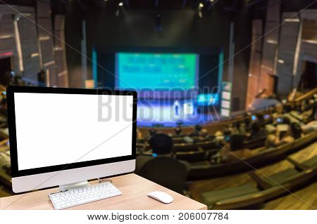 Computer set showing the white screen over the Abstract blurred photo of conference hall or seminar room with attende background business and education concept
