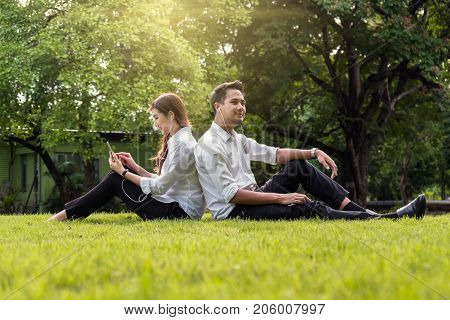 Happy asian couple listening the song via smart phone camera in the park lover and lifestyle concept