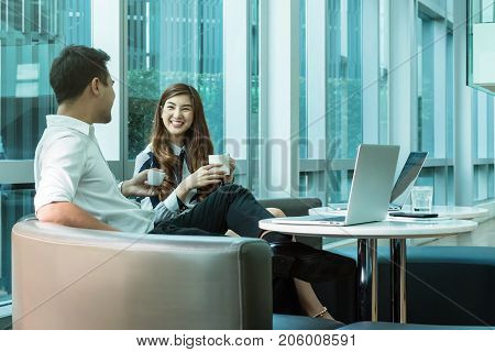 Happy Asian Beautiful young business woman and handsome businessman with formal suits are talking and using a laptop for meeting in modern office business people concept