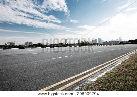 emtpy asphalt road and cityscape of modern city in blue cloud sky