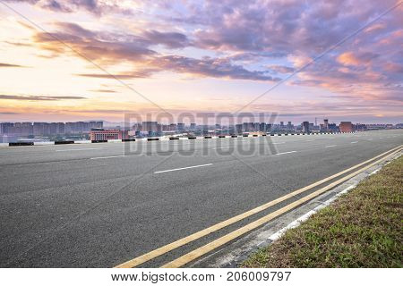 empty asphalt road and cityscape of nanjing in colorful sky