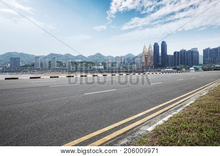 empty asphalt road and modern buildings in nanjing near river in blue sky