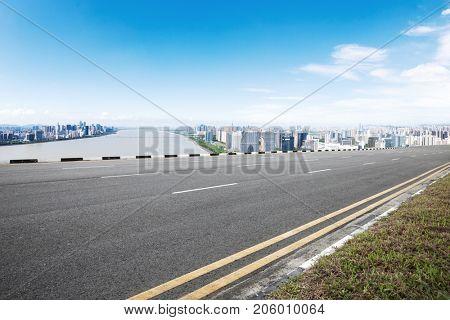 empty asphalt road and cityscpae of hangzhou in blue sky