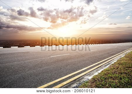 emtpy asphalt road and cityscape of modern city in blue cloud sky at sunrise