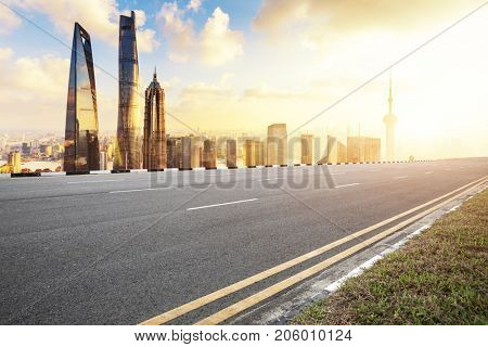 emtpy asphalt road and cityscape of shanghai in blue cloud sky at sunrise