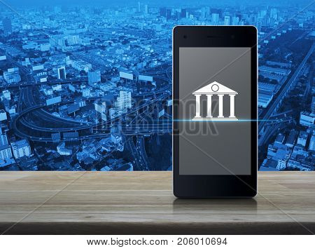 Bank icon on modern smart phone screen on wooden table over city tower street and expressway Mobile banking concept